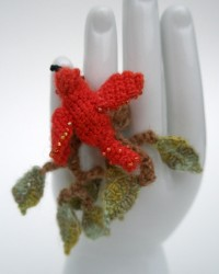 Red bird in branches, ring.  Glass seed beads, crocheted and knitted merino wool.